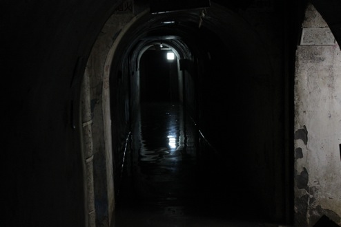 The light in the back is from the production crew; normally the tunnels are pitch dark.
