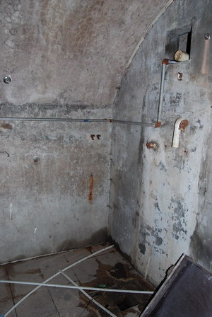 Shower area with drain and pipes in the wall still visible. Image Dan Edwards